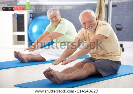 Elderly couple stretching in the gym.