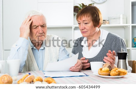Elderly couple studying agreement conditions before signing at home