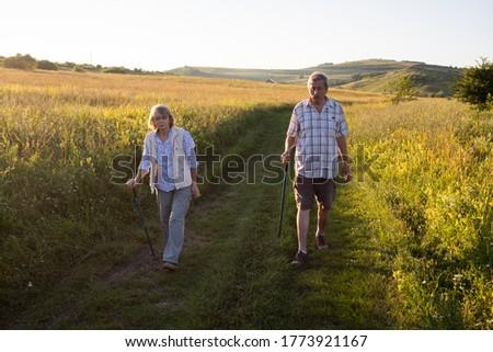 elderly couple trekking in a rural area social distancing