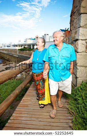 Elderly couple walking on a wooden path holding hands and overlooking the sea.