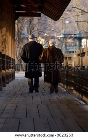 Elderly couple walking on bridge - stock photo