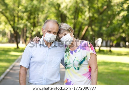 elderly couple wearing medical face mask in the summer garden. health concept. Corona Virus.