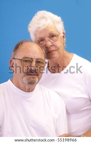 Elderly couple with bright blue background.
