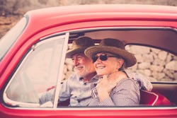 Elderly couple with hat, with glasses, with gray and white hair, with casual shirt, on vintage red car on vacation enjoying time and life. hug together and enjoy the travel of the entire life concept