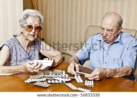 elderly couple with pills - stock photo