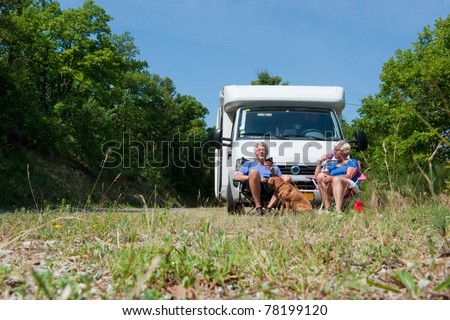 Elderly couple with their dog is travel by camping car