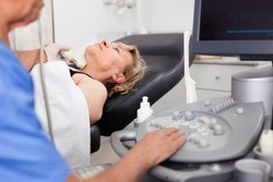 Elderly diligent friendly man sonographer using ultrasonography machine checking female patient in hospital diagnostic room