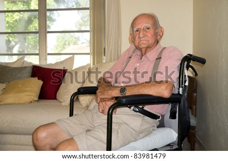 Elderly disabled man in his eighties sitting in a wheelchair inside his home.