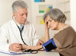 Elderly doctor measuring blood pressure of the senior woman