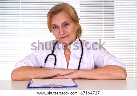 Elderly doctor sitting at the desk - stock photo