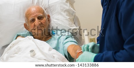 Elderly eighty plus year old man recovering from surgery in a hospital bed.
