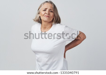 Elderly elegant woman with backache holding backache health problems gray background
