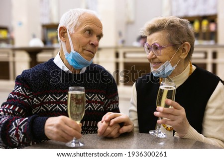 Elderly family in protection masks drinking champagne and relaxing at lobby of theater at intermission Stock photo ©