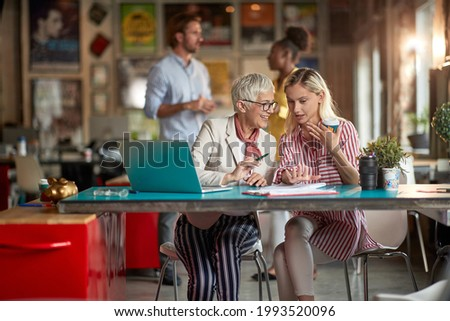 Elderly female boss and her young female colleague enjoying teamwork in a pleasant atmosphere at office. Employees, office, work