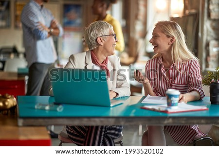 Elderly female boss enjoying a work in a pleasant atmosphere at office with her young female colleague. Employees, office, work