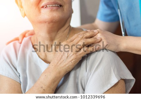 Elderly female hand holding hand of young caregiver at nursing home.Geriatric doctor or geriatrician concept.  Doctor physician hand on happy elderly senior patient to comfort in hospital examination