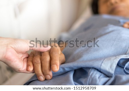 Elderly female hand holding hand of young caregiver at nursing home. Geriatric doctor or geriatrician concept. Doctor physician hand on happy elderly senior patient to comfort in hospital examination