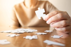 Elderly female hands trying to connect pieces of white jigsaw puzzle on wooden table. Creative idea for Alzheimer's disease, dementia, memory loss and mental health concept. Close up. Copy space.