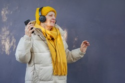 Elderly female listening to music against violet  wall. Senior woman in stylish outerwear listening to music in headphones and dancing against violet wall on city street