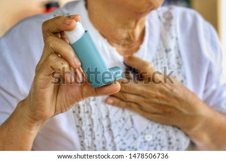 Elderly Female's hand holding inhaler with blurred background.Medication for relief bronchospasm or Dyspnea from asthma attack or allergy,that's an emergency condition.Healthcare and medical concept.