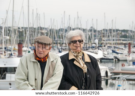 elderly french couple walking together at the yacht harbor of brest in brittany