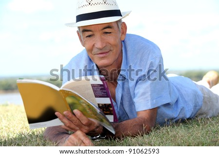 elderly gentleman lying on grass reading tourist guide