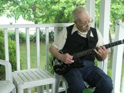 Elderly gentleman playing guitar on his front porch. Focus on face with intentional motion blur on hands.