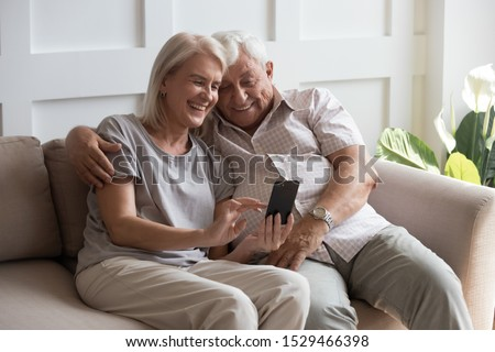 Elderly grandfather and grandmother spend time having fun using smartphone apps, middle-aged wife enjoy online entertainments, taking selfie with old husband, older generation and modern tech concept