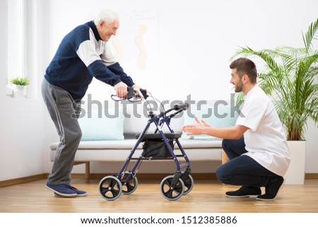 Elderly grandfather with walker trying to walk again and helpful male nurse supporting him Stock photo ©