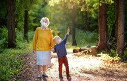 Elderly grandmother and little grandchild wearing facemask walking together in sunny summer park. Grandma and grandson. Two generations of family. Lifting virus lockdown orders. Social distancing.