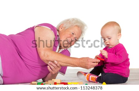 Elderly grandmother lying on the floor babysitting her small grandchild as the two play contentedly together with toy blocks
