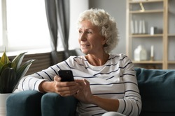 Elderly grandmother resting on couch holding in hands smart phone distracted from chatting with grown up children looking out the window enjoy day feels healthy. Older generation using gadgets concept
