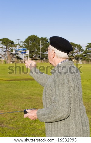 Elderly great-grandfather in his 80's, playing with a small remote controlled airplane on a sports field.