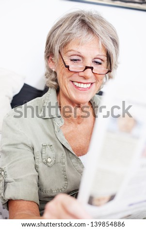 Elderly grey haired lady wearing a pair of reading glasses sitting reading the newspaper with a smile
