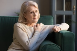 Elderly grey-haired pensive depressed woman sit on sofa alone at home lost on sad thoughts, grandmother thinking about problems difficulties, having senile diseases, mental emotional disorders concept