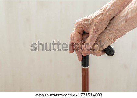 Elderly hands resting on stick. Close up hands of old woman holding walking stick. Hands of woman pensioner on a walking stick closeup. Old lady holding walking stick. Concept of help in old age
