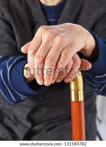 Elderly hands resting on the walking stick