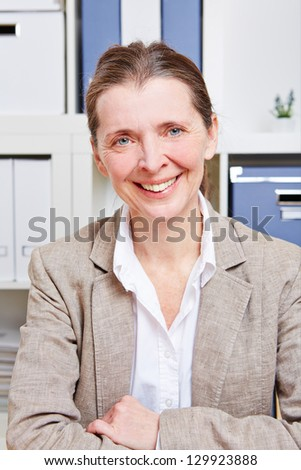 Elderly happy business woman sitting in her office at her desk