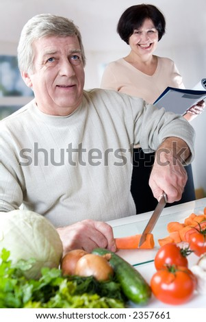 Elderly happy couple cooking at kitchen
