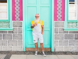 Elderly hipster traveling and looking at his smartphone - Senior man wearing trendy dungarees - Concept of senior enjoy technology