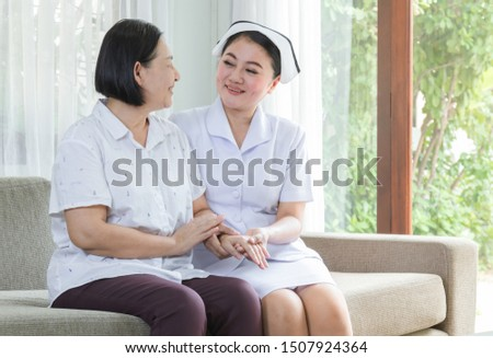 Elderly hold hand with caregiver of nurse in home on sofa. Elder smile and happy concept