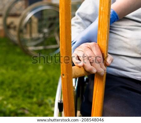 Elderly homecare - nurse handing crutch to sick patient.