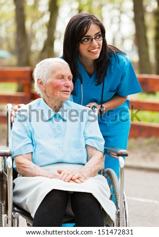 Elderly lady and nurse looking at the arriving visitors