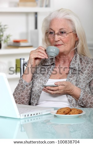 Elderly lady drinking coffee and using laptop