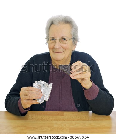 Elderly lady enjoys eating chocolate, white background - great expression