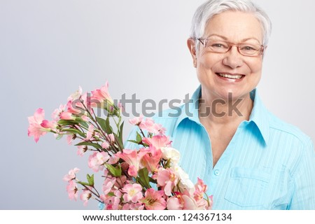 Elderly lady holding flowers at mother's day, smiling.