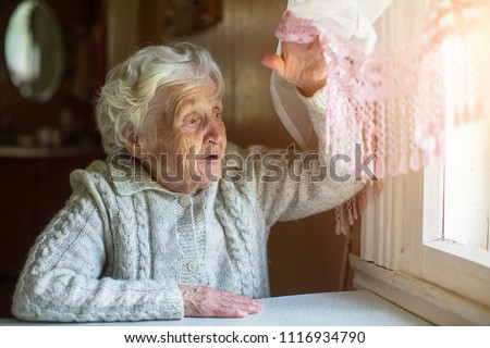 Elderly lady looks out of the window with a hand opening the curtain.