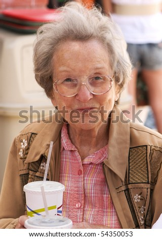 Elderly lady of 88 years having lunch outdoors at a taco stand