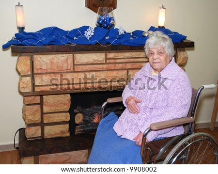 Elderly lady sitting in front of a fireplace