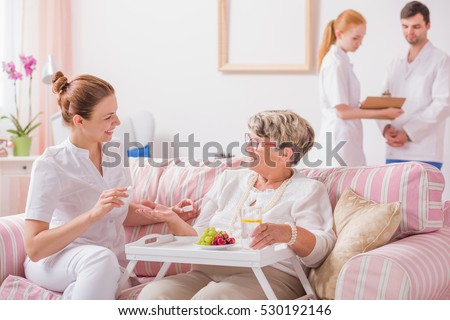 Elderly lady sitting on a couch with a tray and a young nurse giving her medicines in private clinic